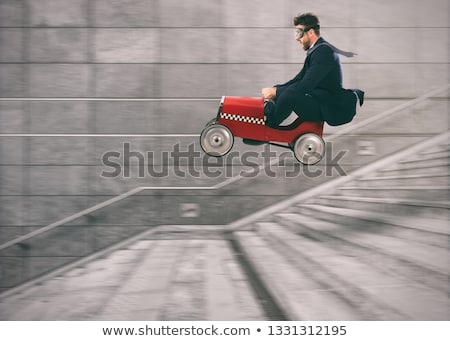 Reckless business man goes down the stairs with a car to get before the others. Concept of success a Stock photo © alphaspirit