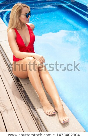 Young fit attractive female in red swimwear sitting by poolside Stock photo © pressmaster