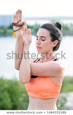 Peaceful young woman with closed eyes twisting arms while doing eagle pose Stock photo © pressmaster