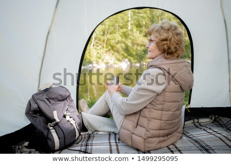 Active mature female backpacker with hot drink sitting in tent Stock photo © pressmaster