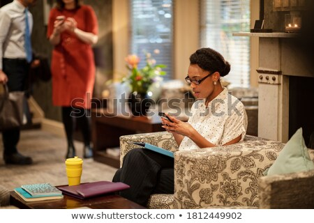 businesswoman using smart phone sitting with her colleagues stock photo © andreypopov