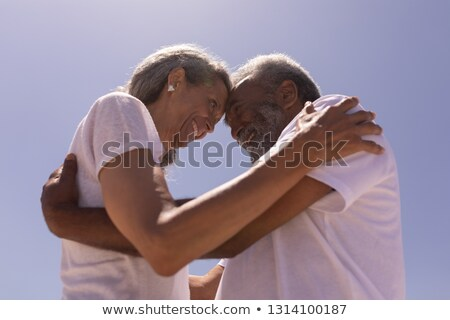 Low angle view of happy senior couple head to head and embracing each other on beach in the sunshine Stock photo © wavebreak_media