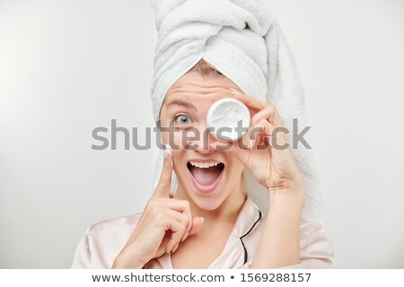 Excited girl with towel on head holding jar of facial hydrating cream by eye Stock photo © pressmaster