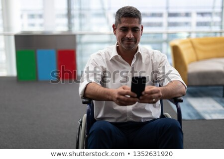 Front view of mature Caucasian disabled businessman using mobile phone while sitting on wheelchair i Stock photo © wavebreak_media