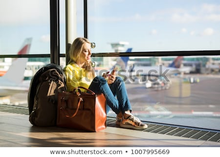 Young woman with her luggage at an international airport, waitin Stock photo © lightpoet