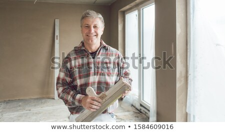 Friendly plasterer in the interior of newly constructed house Stock photo © Kzenon