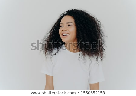 Portrait of beautiful curly adult woman turns gaze aside, has glad expression, smiles and laughs at  Stock photo © vkstudio