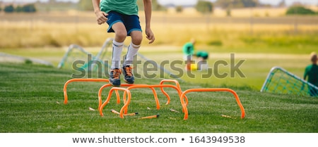 Low section portrait of unrecognisable boy jumping over hurdles  Stock photo © matimix