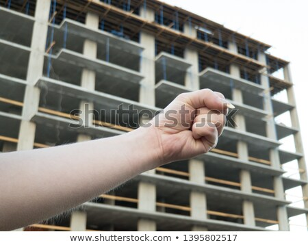 A hand holding a foreman helmet over the sky Stock photo © Lopolo
