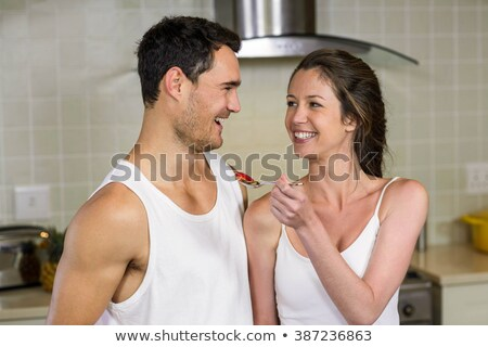 Happy young couple feeding each other with strawberries Stock photo © deandrobot