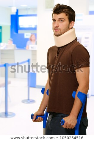 Painful expression of young guy walking with help of crutches Stock photo © stockyimages