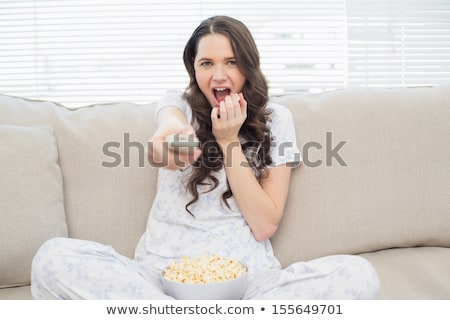 Gorgeous women lounging on a sofa watching a movie in a living room Stock photo © wavebreak_media