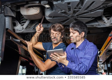 Concentrated mechanic repairing a car while using tools in a garage Stock photo © wavebreak_media