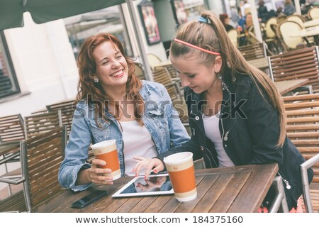 Two Teenage Girls Using Digital Tablet In Outdoor cafe Stock photo © monkey_business