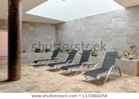Grey empty chaise lounges in hotel area. Stock photo © kyolshin