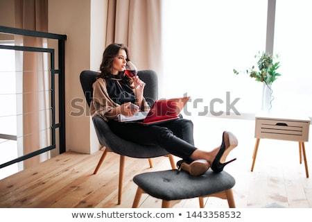 Jóvenes mujer de negocios potable vino tinto sesión sillón Foto stock © nyul