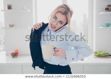 Business woman putting on jacket Stock photo © HASLOO