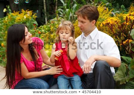 Little girl in red dress blows soap bubbles in summer garden together with parents. stock photo © Paha_L