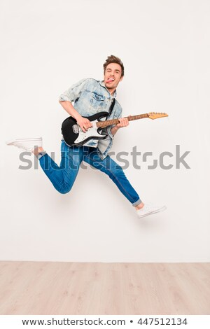 crazy young guitarist playing electric guitar and shoing tongue stock photo © deandrobot