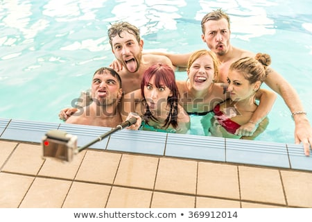 group of best friends having party by swimming pool stock photo © deandrobot