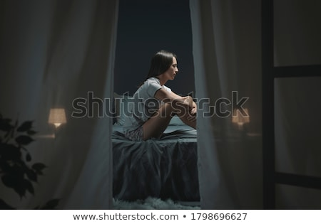 depressed woman sitting on bed in bedroom stock photo © deandrobot