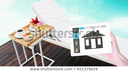 Hand holding digital tablet with smart home application on screen at poolside Stock photo © wavebreak_media
