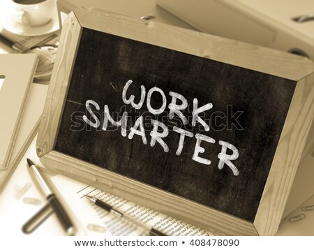 work smarter handwritten by white chalk on a blackboard stock photo © tashatuvango