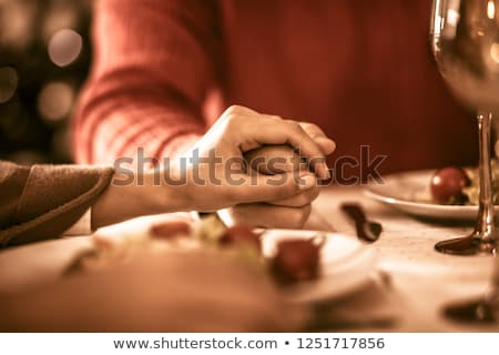Group of people holding hands and praying at dinner table Stock photo © deandrobot