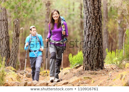 man and woman happy couple hikers walking in autumn woods stock photo © blasbike