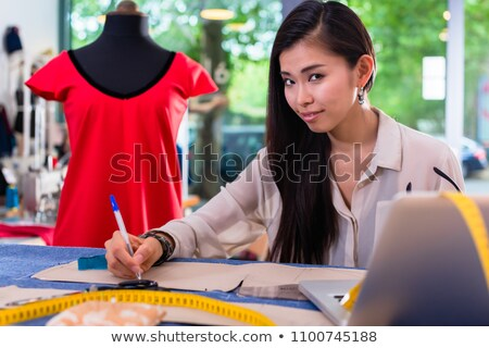 Asian fashion designer preparing drafts for cut-outs Stock photo © Kzenon