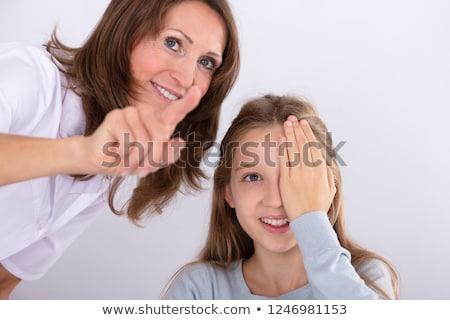 Optometrist Assisting Girl While Checking Eyesight Stock photo © AndreyPopov