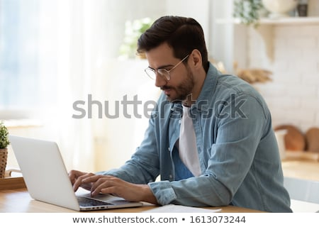 Busy young man working on laptop computer at home Stock photo © deandrobot
