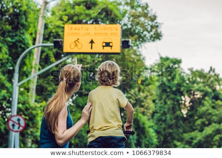 Mom shows his son a plate of shared lane and beware bike warning sign Stock photo © galitskaya