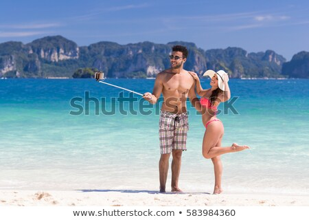 mixed race couple taking picture by selfie stick Stock photo © dolgachov
