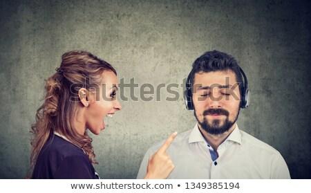 Mérges nő kiabál higgadt férj zenét hallgat Stock fotó © ichiosea