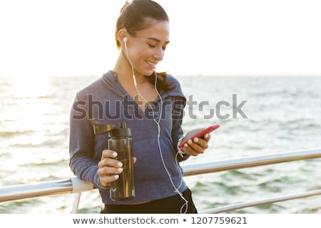 Amazing strong sports woman standing on the beach listening music holding water chatting by phone. Stock photo © deandrobot
