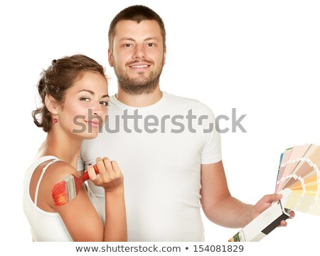 Image of cheerful couple man and woman holding paint rollers and Stock photo © deandrobot