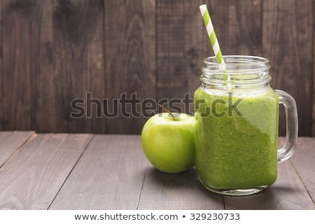 Green apple smoothie in glass and kale leaves on wooden table stock photo © AbstractVanilla