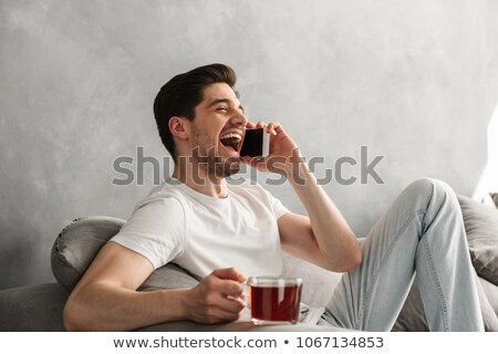 Positive brunette man in basic t-shirt laughing while talking on Stock photo © deandrobot