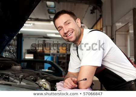 handsome mechanic based on car in auto repair shop Stock photo © Lopolo