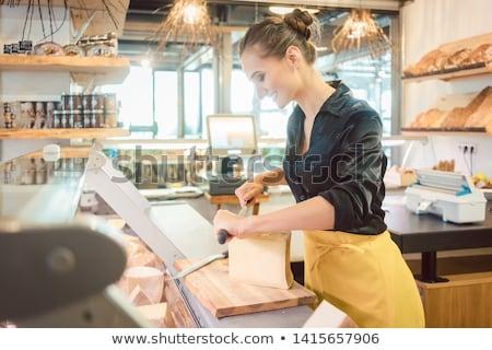 Shop clerk in deli cutting cheese Stock photo © Kzenon