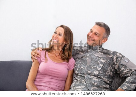 army man with his wife sitting on sofa looking away stock photo © andreypopov