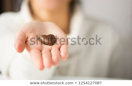 close up of hand with heart shaped chocolate candy Stock photo © dolgachov