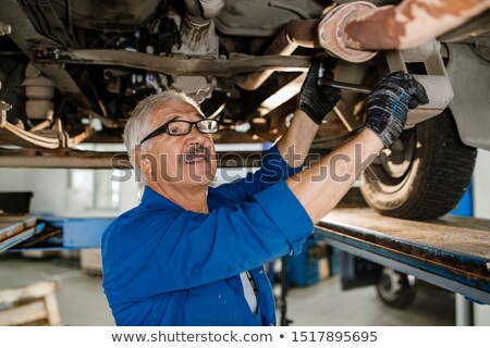 Senior technician of repair service with worktool fixing details of car Stock photo © pressmaster