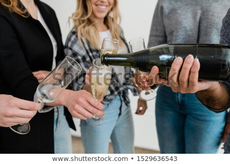 young man with bottle of champagne pouring the dfrink into one of flutes stock photo © pressmaster