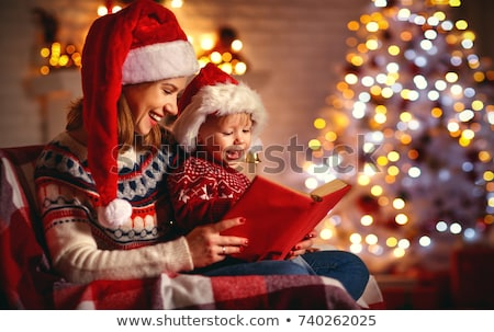 baby girl reading a book at christmas stock photo © liolle