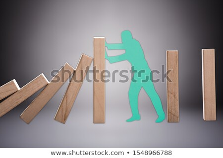Cut Out Human Figure Stopping The Wooden Domino To Fall Stock photo © AndreyPopov