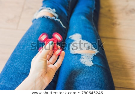 Girl teenager in holey jeans holds in hands and plays with spinner Stock photo © galitskaya