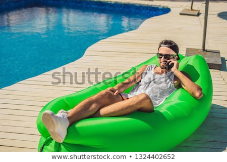 Young man enjoying leisure, lying on the air sofa Lamzac, near the pool Stock photo © galitskaya
