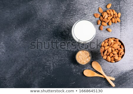 Fresh almond milk in wooden bowl and almonds on black stone background Stock photo © dash